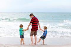 Deux garçons et père de petits enfants sur la plage de l'océan Photo stock