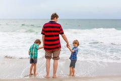 Deux garçons et père de petits enfants sur la plage de l'océan Photo libre de droits