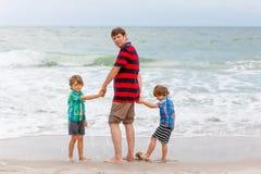 Deux garçons et père de petits enfants sur la plage de l'océan Image libre de droits