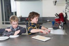 Deux garçons faisant la vaisselle Image stock