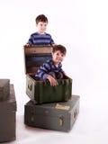 Deux garçons, frères, jouant avec des boîtes sur le fond blanc Photographie stock libre de droits
