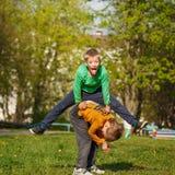 Deux garçons gais jouent dehors, sautent l'ami par le fri Images libres de droits