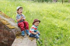 Deux garçons gais s'asseyent sur une pelouse verte en parc pendant l'été Photographie stock libre de droits