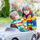Deux garçons heureux d'enfant de mêmes parents jouant avec la grande vieille voiture de jouet Photos stock