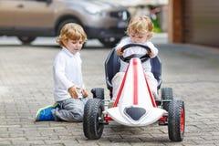 Deux garçons heureux d'enfant de mêmes parents jouant avec la voiture de jouet Image stock