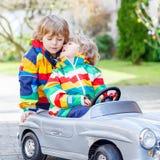 Deux garçons heureux d'enfant de mêmes parents jouant avec le grand vieux jouet Images stock