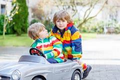 Deux garçons heureux d'enfant de mêmes parents jouant avec le grand vieux jouet Image libre de droits