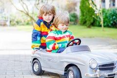 Deux garçons heureux d'enfant de mêmes parents jouant avec le grand vieux jouet Photos stock