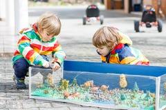 Deux garçons heureux d'enfant de mêmes parents jouant avec les jouets sodier Photos stock