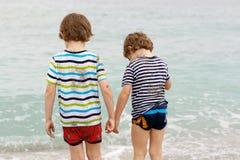 Deux garçons heureux de petits enfants courant sur la plage de l'océan Image libre de droits