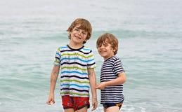 Deux garçons heureux de petits enfants courant sur la plage de l'océan Photographie stock