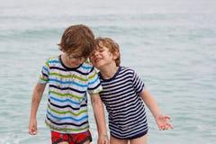 Deux garçons heureux de petits enfants courant sur la plage de l'océan Image stock