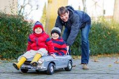 Deux garçons heureux et père d'enfant de mêmes parents jouant avec la grande vieille voiture de jouet, Photos libres de droits