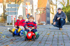 Deux garçons heureux et père d'enfant de mêmes parents jouant avec la grande vieille voiture de jouet, Image libre de droits