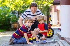 Deux garçons heureux et père de petit enfant réparent la chaîne sur les vélos et la roue de changement de la bicyclette d'équilib Photos libres de droits