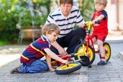 Deux garçons heureux et père de petit enfant réparent la chaîne sur les vélos et la roue de changement de la bicyclette d'équilib Photo libre de droits