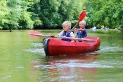 Deux garçons heureux kayaking sur la rivière Photos stock