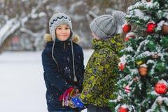 Deux garçons heureux ou des amis s'approchent de l'arbre de Noël extérieur Photographie stock libre de droits