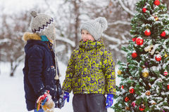 Deux garçons heureux ou des amis s'approchent de l'arbre de Noël extérieur Photographie stock
