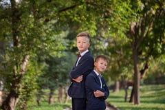 Deux garçons heureux se tenant de nouveau au dos sur le fond de nature dans le jour d'été photographie stock