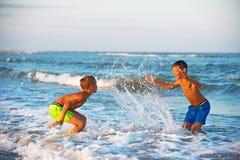 Deux garçons jouant à la plage avec de l'eau Photographie stock libre de droits