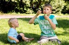 Deux garçons jouant dans le jardin photographie stock
