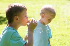 Deux garçons jouant dans le jardin Photographie stock libre de droits