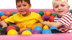 Deux garçons jouant dans un puits de boule clips vidéos