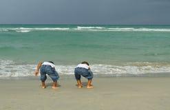 Deux garçons jouant par le rivage images stock