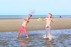 Deux garçons jouant sur la plage Image stock