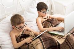 Deux garçons jouent à l'ordinateur portable et au comprimé avec le chien dans le lit Images libres de droits