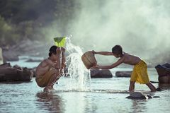 Deux garçons jouent l'éclaboussure dans le courant Images libres de droits