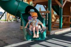 Deux garçons jouent sur le terrain de jeu photos stock