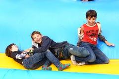 Deux garçons jouent sur le trempoline en parc extérieur d'amusement d'été Images libres de droits