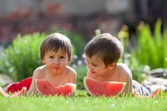 Deux garçons, mangeant la pastèque dans le jardin Photos libres de droits