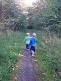 Deux garçons marchant sur un chemin forrest Image stock
