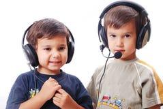 Deux garçons mignons avec des écouteurs en fonction Photos libres de droits