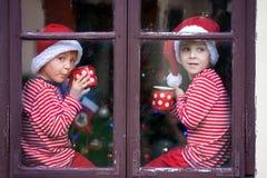Deux garçons mignons, frères, regardant par une fenêtre, S de attente Images libres de droits