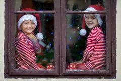 Deux garçons mignons, frères, regardant par une fenêtre, S de attente Photos stock