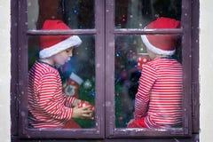 Deux garçons mignons, frères, regardant par une fenêtre, S de attente Photographie stock libre de droits
