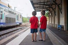 Deux garçons, observant un train laisser une station Image libre de droits