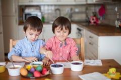 Deux garçons, oeufs de coloration pour Pâques Photos stock