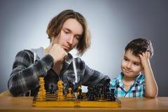 Deux garçons ou frères jouant des échecs d'isolement sur le fond gris Images libres de droits