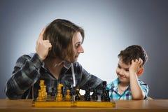 Deux garçons ou frères jouant des échecs d'isolement sur le fond gris Image stock