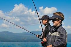 Deux garçons pêchant avec le fond de ciel bleu. Photographie stock libre de droits