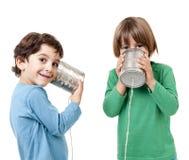 Deux garçons parlant à un téléphone de boîte en fer blanc Photo stock