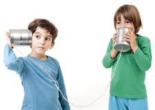 Deux garçons parlant à un téléphone de boîte en fer blanc Images stock