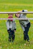 Deux garçons penchés sur une barrière Image stock