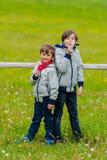 Deux garçons penchés sur une barrière Photographie stock