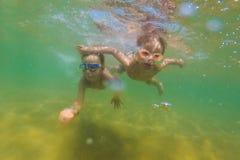 Deux garçons plongent dans des lunettes de natation en mer Photographie stock libre de droits